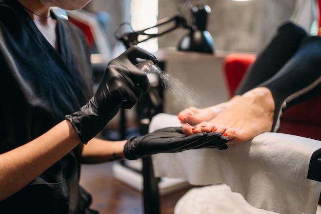 Il maestro di pedicure in guanti neri spruzza le unghie dei piedi del cliente femminile, salone di bellezza. cura professionale delle unghie