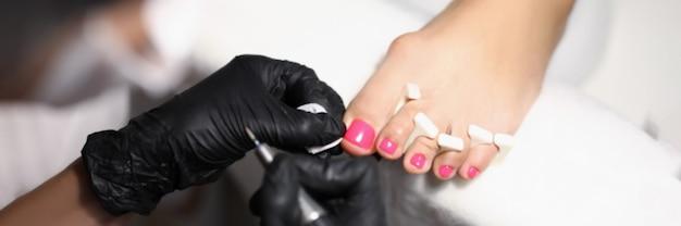 Il maestro di pedicure con i guanti rende la correzione delle unghie dei piedi delle donne le mani del maestro wipe