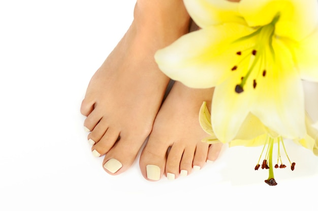Pedicure con gigli gialli su sfondo bianco.