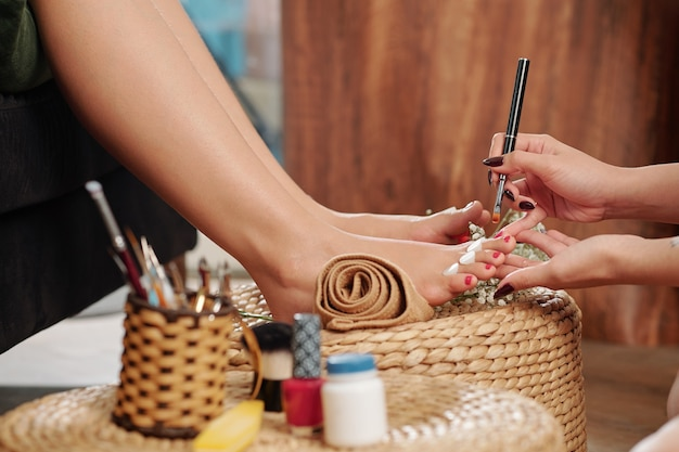 Pedicurist che applica olio per cuticole
