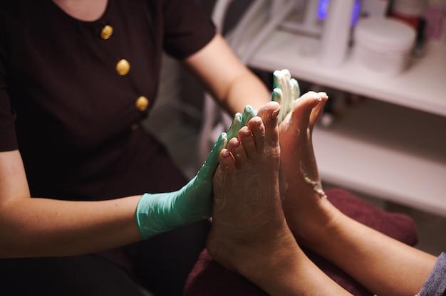 Pedicurist che applica crema idratante nutriente sulle gambe della donna e massaggiandole nella sala pedicure