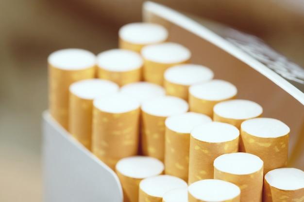 Staccalo pacchetto di sigarette prepara fumando una sigaretta. linea di imballaggio. filtri fotografici luce naturale. focalizzazione morbida