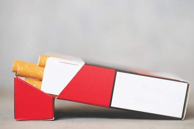 Staccalo pacchetto di sigarette prepara il fumo su fondo di legno bianco