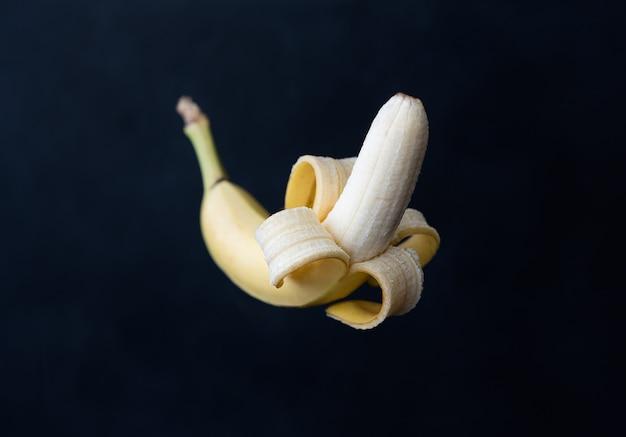 Banana sbucciata su uno sfondo nero