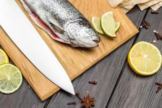 Trota di pesce sbucciata e coltello sul tagliere. spicchi di limone sul tavolo. lay piatto
