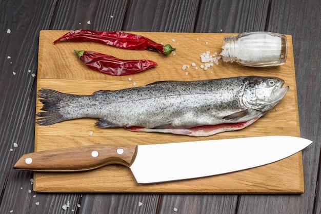 Trota di pesce sbucciata, carta rossa, sale e coltello sul tagliere. vista dall'alto