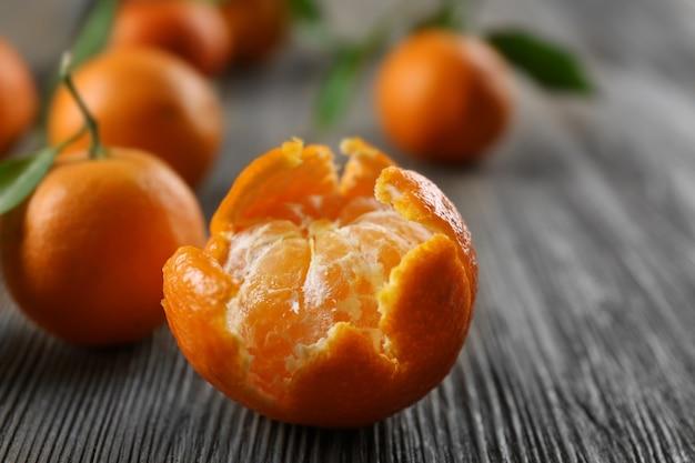 Mandarini freschi sbucciati con le foglie ed i mandarini maturi sulla tavola di legno, primo piano