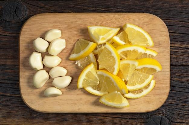 Aglio sbucciato e limone affettato in piatto su un tagliere di legno, vista dall'alto. mangiare sano