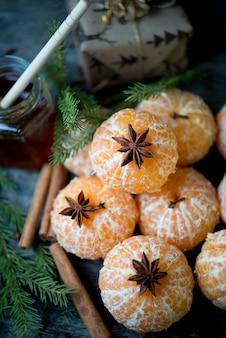 Mandarini sbucciati, spezie e rami di alberi di natale