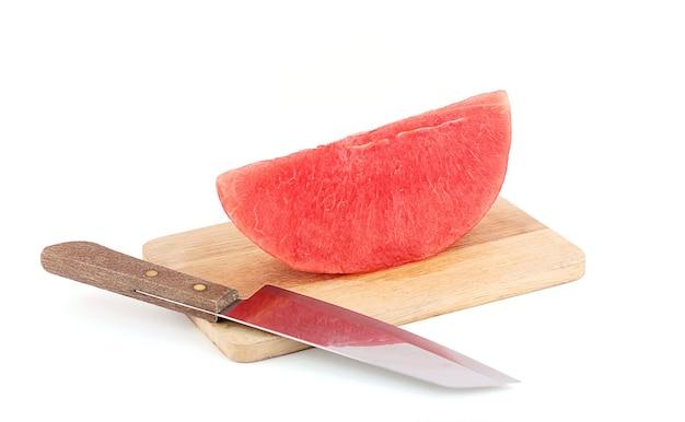 L'anguria sbucciata viene posta sul tagliere con un coltello per tagliare.