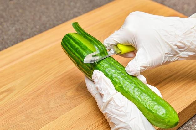 Sbucciare il cetriolo, donna in guanti di gomma sbucciare la buccia di cetriolo, stile di vita sano e concetto di dieta