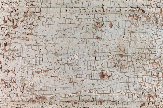 Vernice scrostata sul muro. vecchia struttura del muro con la vernice bianca scrostata da vicino.