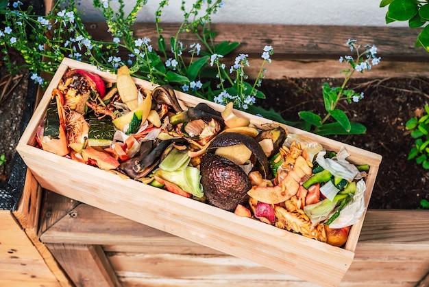Bucce e rifiuti organici in una cassa di legno per creare compost fatto in casa.