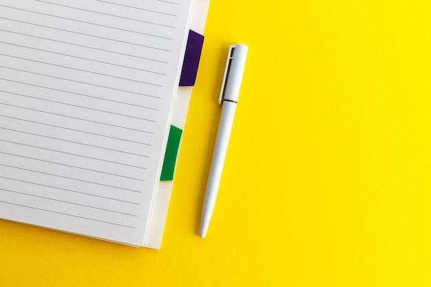 Penna e blocco note in bianco su giallo