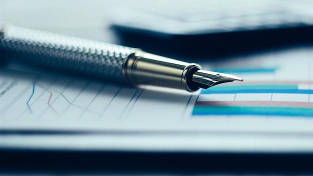 Calcolatrice penna e grafico finanziario su un posto di lavoro