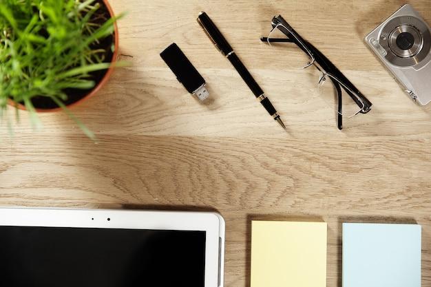 Penna, tavoletta digitale e carta per appunti su fondo in legno