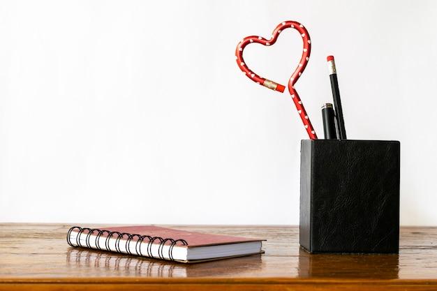 Portapenne con matita a forma di cuore sul tavolo, con taccuino a spirale.