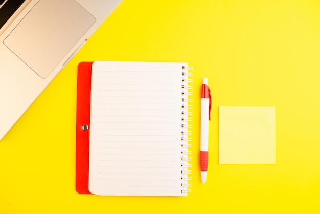 Penna, computer portatile, pianificatore del blocco note e blocco note su fondo giallo.