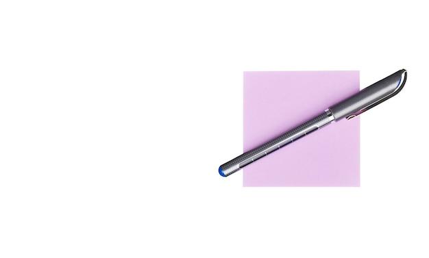 Penna che si trova su una nota di adesivo, isolata