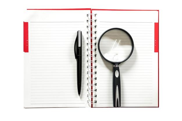 Penna e lente d'ingrandimento che riposa su un taccuino