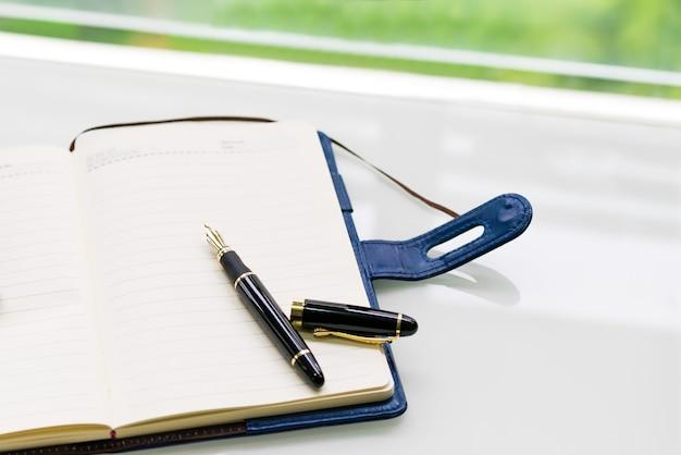 Penna e taccuino sul tavolo bianco vicino alla finestra, sideview con sfondi verdi