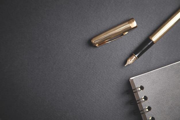 Penna e blocco note sulla tavola nera.