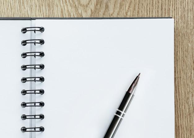 Penna e blocco note sulla scrivania in legno. concetto di affari, foglio bianco con posto per pubblicità e scritte. forniture per istruzione e formazione. Foto Premium