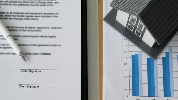 Penna posizionata su documenti contrattuali e case modello su grafici di dati, firma di contratti per la costruzione e l'acquisto di case, primo piano e vista dall'alto..