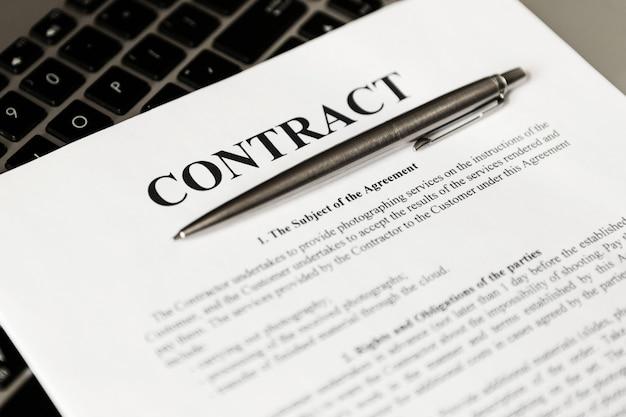 Penna per la firma del contratto. la penna e il contratto sono sul laptop.