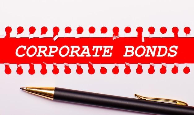 Penna e striscia di carta bianca strappata su uno sfondo rosso brillante con il testo obbligazioni aziendali