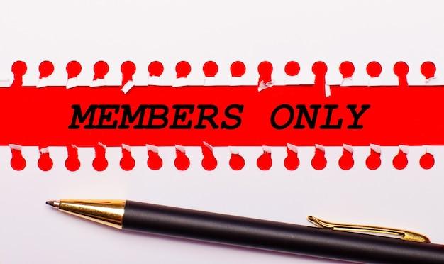 Penna e striscia di carta bianca strappata su uno sfondo rosso brillante con il testo solo membri