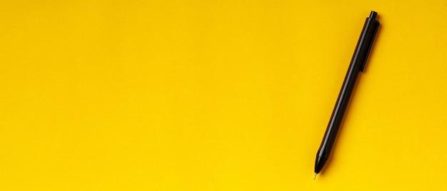 Una penna su sfondo giallo con copia spazio