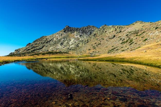 Il picco di penalaras si riflette su un lago glaciale