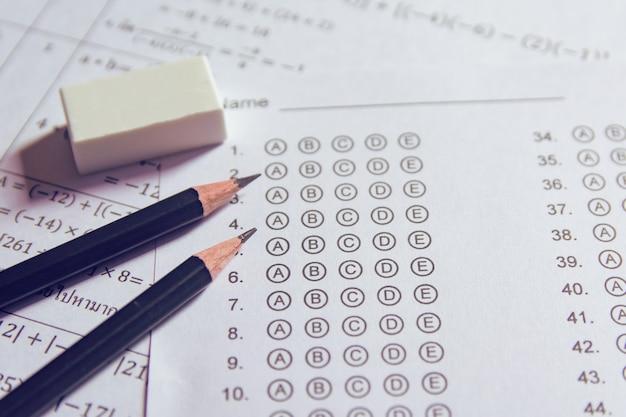 Matita e gomma sui fogli delle risposte o modulo di prova standardizzato con le risposte ribollite. foglio risposte a scelta multipla