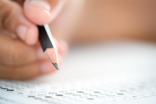 Matita a portata di mano che scrive risposta della domanda esame di prova su carta di risposta