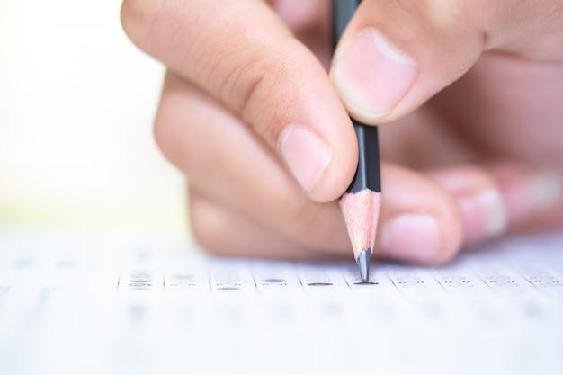 Matita a portata di mano, scrivendo la risposta della domanda di esame del test
