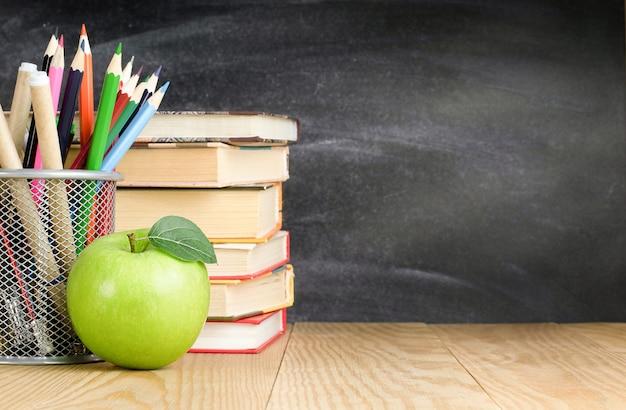 Portamatite, libri e mela su un tavolo di legno, torna al concetto di scuola
