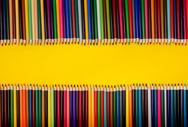 Matite di diversi colori dell'arcobaleno su sfondo giallo