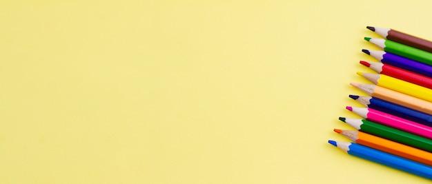 Matite per disegnare su uno sfondo giallo.