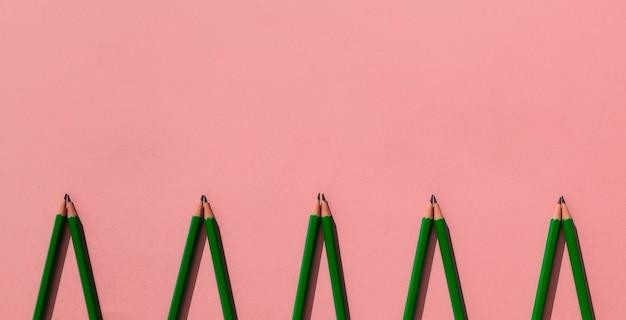 Cornice di matite su sfondo rosa