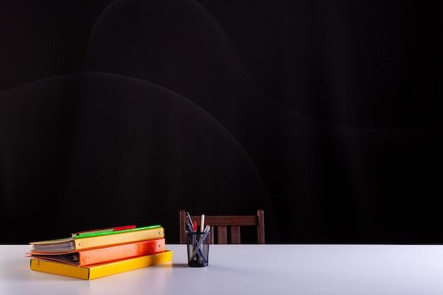 Pentola per matite accanto ai libri impilati, materiale scolastico sulla scrivania bianca con trama di lavagna sullo sfondo. vista laterale, copia dello spazio. apprendimento, concetto di educazione