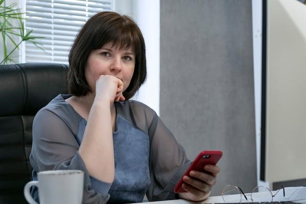 Pencive donna si siede sul posto di lavoro con lo smartphone. smm manager funzionante. promozione dei social network.