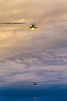 Lampada a sospensione appesa all'aperto con sfondo nuvoloso cielo blu