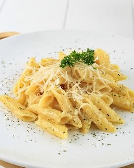 Penne alla carbonara cremoso e ricco di pasta italiana con formaggio e prezzemolo in cima. primo piano sul piatto bianco