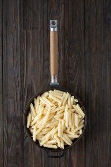Penne pasta italiana in padella, stile rustico.