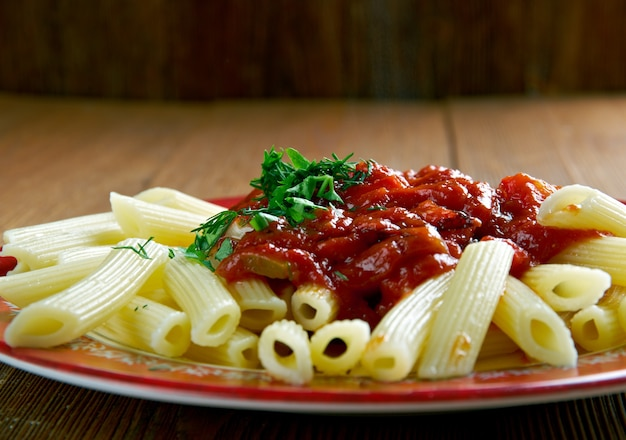 Penne al sugo arrabiata. salsa piccante per pasta a base di aglio, pomodoro e peperoncino cotto in olio d'oliva