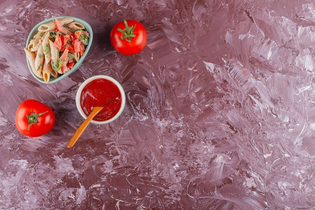 Pasta di penne con salsa di pomodoro e pomodori rossi freschi su un tavolo luminoso.