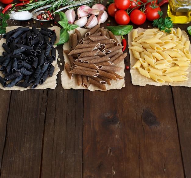 Pasta di penne con verdure, erbe aromatiche e olio d'oliva su fondo in legno