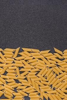 Penne rigate su sfondo grigio. sfondo di pasta cruda. cornice verticale