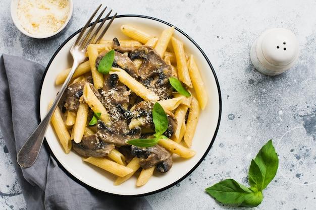 Penne rigate con funghi, parmigiano e foglie di basilico in un piatto di ceramica sul vecchio tavolo in cemento chiaro.